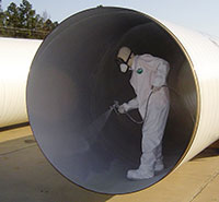 Man in protective suit spraying coat on pipe interior.
